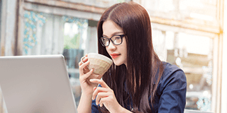 Woman sipping on coffee at computer